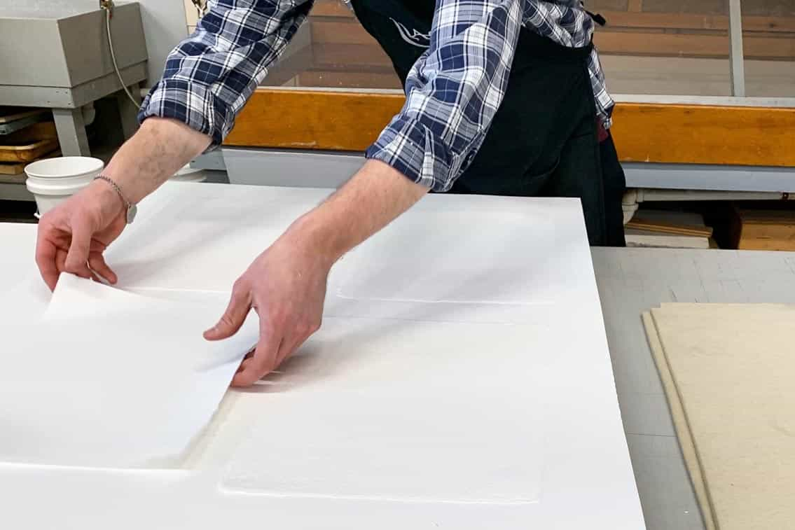Printer Michael Rahn placing handmade sheets of paper on blotters for the drying box.